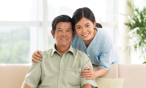 an elderly man with a caregiver woman